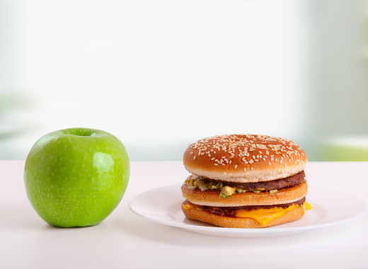 choice of healthy and unhealthy food. Diet concept: green apple and hamburger