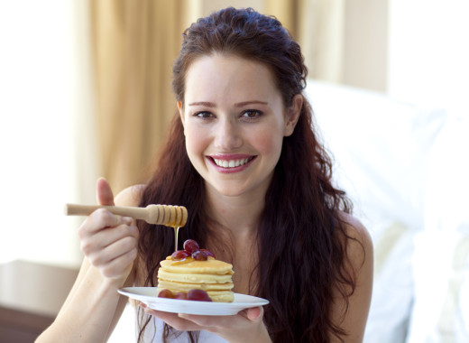 Happy woman eating a sweet dessert in bedroom